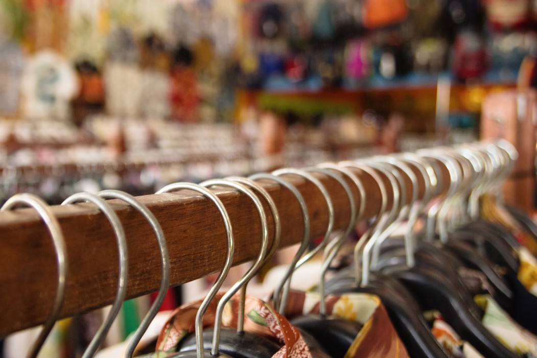 wooden-clothes-racks-with-hangers-and-with-colorful-clothes-on-a-blurred-background-inside-a-shop_t20_lorNGb